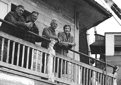 Pictured from left: Dundas Leavitt, Gus Van Lennep, (unidentified person), and Vida Van Lennep, as seen on the 1879 Hooper Strait Lighthouse, after it was moved by barge and relocated to the Chesapeake Bay Maritime Museum, c. 1966. Built to make the Chesapeake Bay safer for navigation, the 1879 Hooper Strait Lighthouse replaced an 1867 lighthouse that had been destroyed by ice. When rebuilt, Keeper John Cornwell resumed his position, undaunted by the harrowing experience of escaping the sunken lighthouse across ice-choked waters. After automation in 1954, the Coast Guard no longer needed the living quarters and, in 1966, planned to demolish the wooden house. The Museum purchased it from the demolition contractor and moved it by barge to St. Michaels, opening it as an exhibition in 1967.