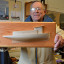 CBMM Model Guild President and volunteer Bob Mason holds an example of the half-hull model that will be made in the October 17 & 18, 2015 workshop.